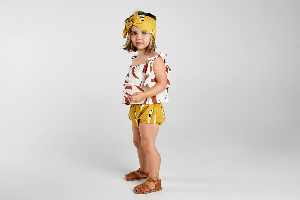 toddler wearing terracotta paint stripe camisole with bather girl bloomers