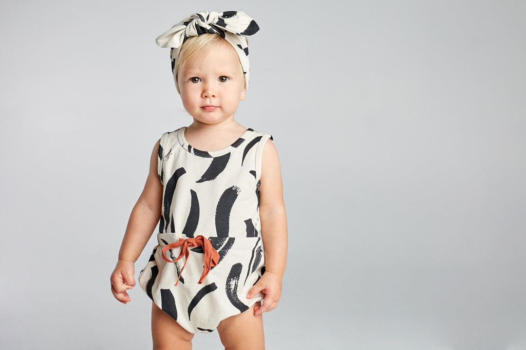 toddler girl wearing mad about mini black and white headband and matching romper