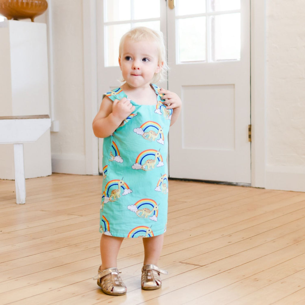toddler wearing handmade green tunic dress with rainbows and unicorn dinosaurs
