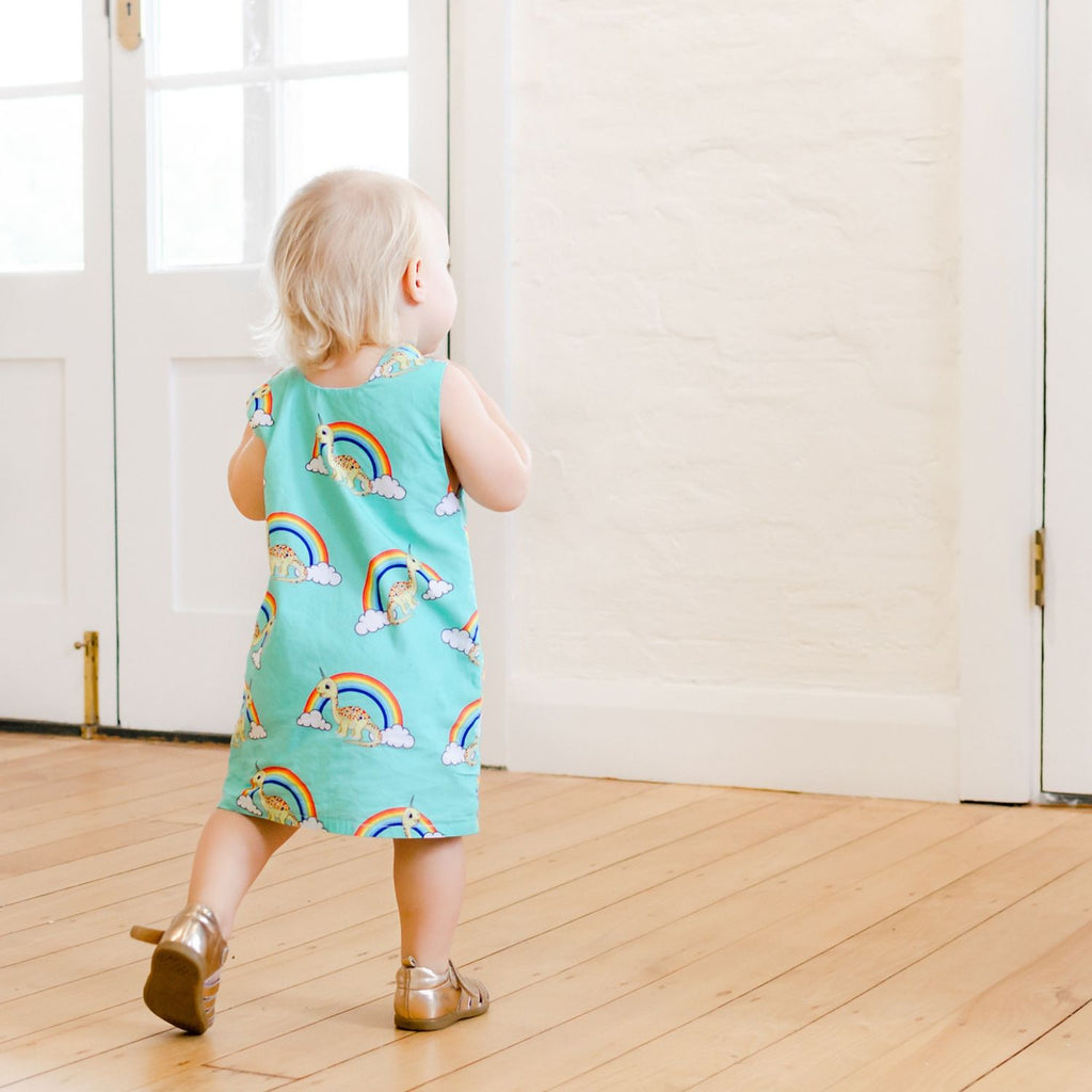 back of girl wearing handmade green tunic dress with rainbows and unicorn dinosaurs