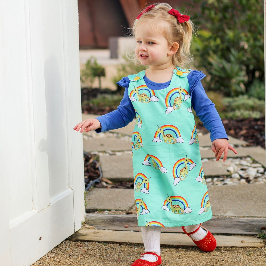 girl wearing handmade tunic dress with rainbows and unicorns