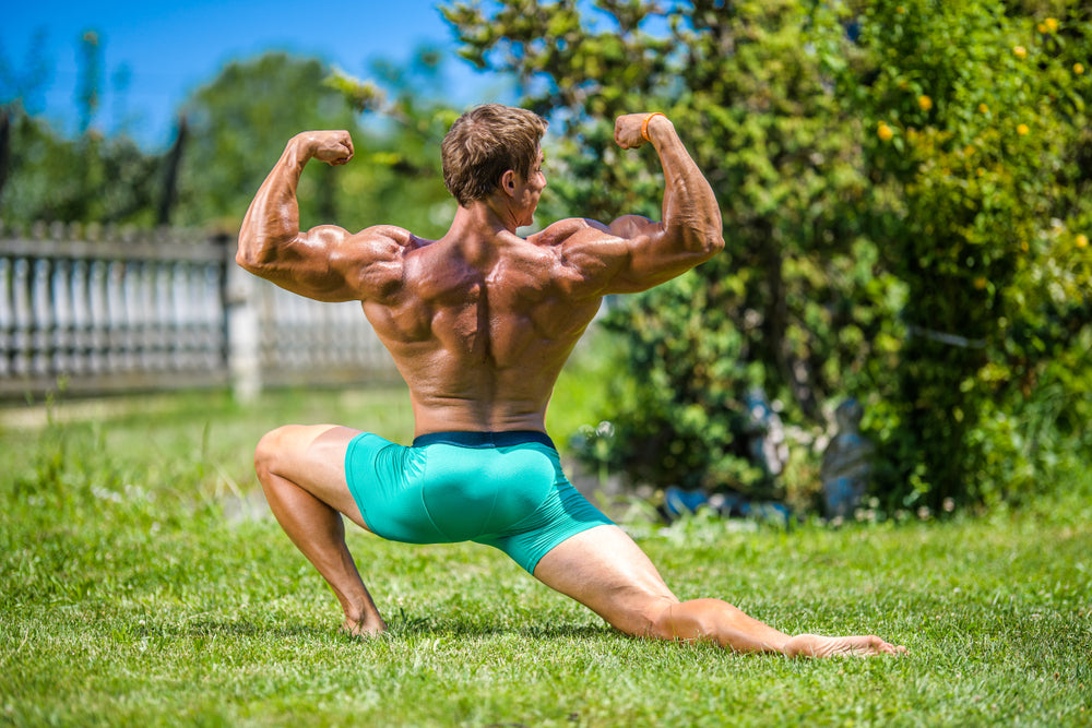 a bodybuilder in posing in nature