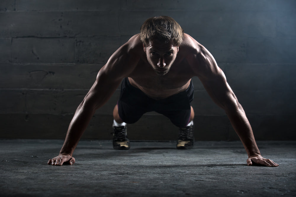 Athlete with a beautiful body and a naked torso doing push-ups exercise on the floor.