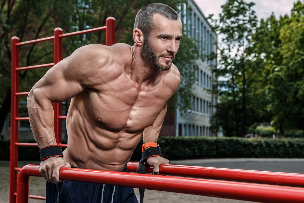 Muscular man doing dips outdoors