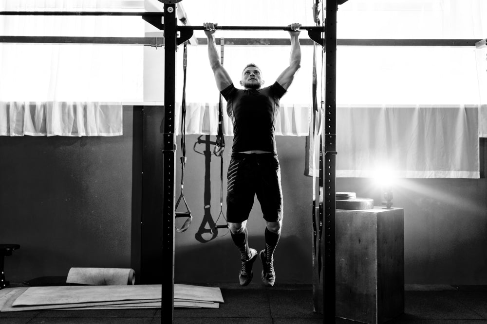Muscular bearded man doing a dead hang in a gym.