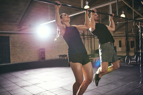 Man and woman in gym doing pull-ups.