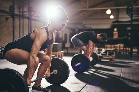 Man and woman doing deadlifts.