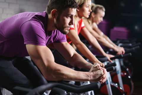 Man and woman on indoor spin bikes.