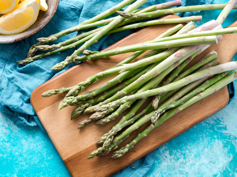 Asparagus on a wooden cutting board with lemon.