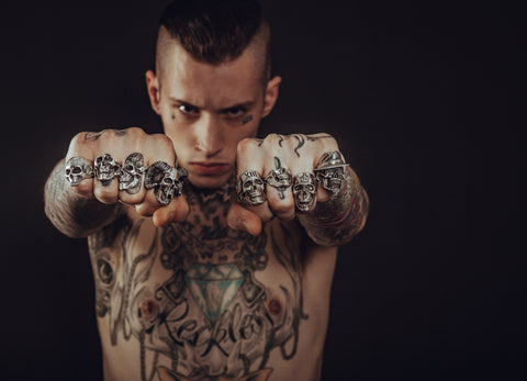 A man with rings and tatoos.