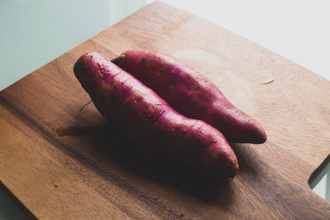 Sweet potato on a wooden cutting board.