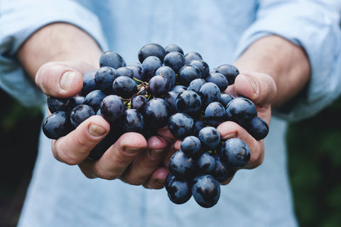 A person holding grapes.