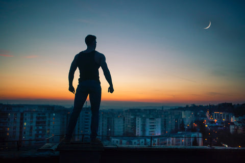 A silhouette of a strong man overlooking a city during sunrise.