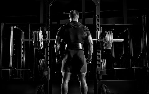 man stands in front of squat rack in gym