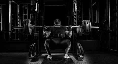man doing barbell squats in a gym