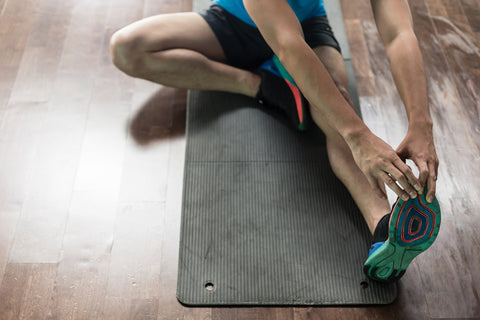 man stretching hamstrings on exercise mat