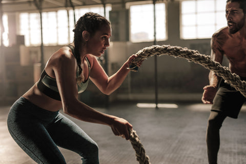 A girl working out with a rope in the gym.