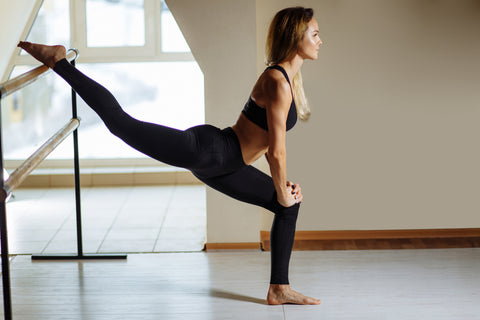 woman stretching her legs on a barre in a workout studio