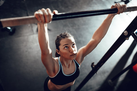 A girl doing pull-ups in the gym.