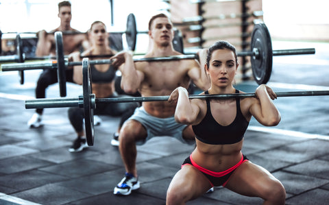 Group of sporty muscular people are working out in gym.