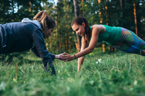 Two girls doing clapping push-ups outdoors