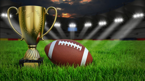 American football arena with ball and trophy cup on green grass