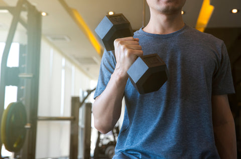 Young man beginner exercising with dumbbell