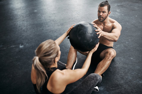 Two fit young people in sportswear sitting on a gym floor working out together with a medicine ball
