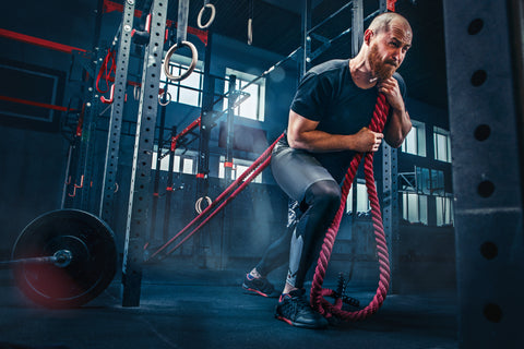 Man with battle rope battle ropes exercises in the gym