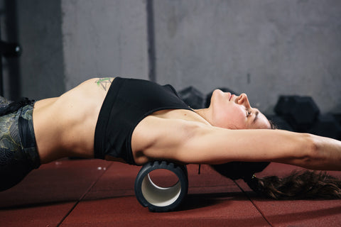 sportswoman uses a foam roller massager for relaxation, stretching muscles and back pain
