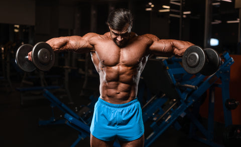 Handsome young fit muscular caucasian man of model appearance workout training in the gym