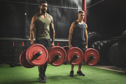 Two muscular men during competition in the farmer's walk exercise