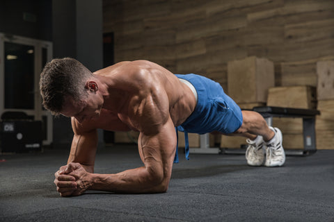muscular man doing a plank in a gym