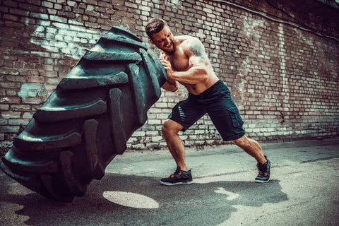 Muscular bearded tattooed fitness shirtless man moving large tire in street gym