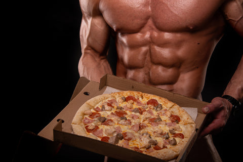 Muscular bodybuilder holding a pizza