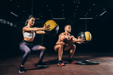 A man and woman doing squats with medicine balls.