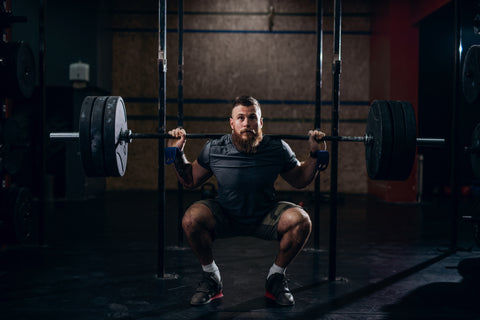 A man doing a back squat.
