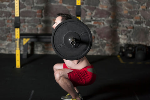 Topless male athlete practicing olympic lifts at gym with brick wall background.