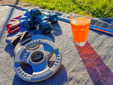Dumbbells, resistance rubber bands, metal weight plates next to glass of preworkout drink on the towel in sunny morning