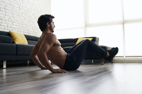 A man doing crunches in his apartment.