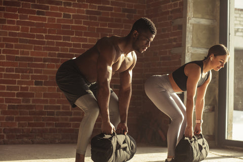 Young mixed-race fit couple doing sandbag bent over rows
