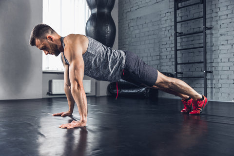 A man doing push ups in a gym.