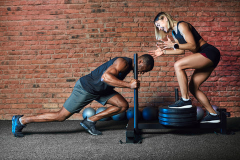 A man and woman working out with a weight sled.