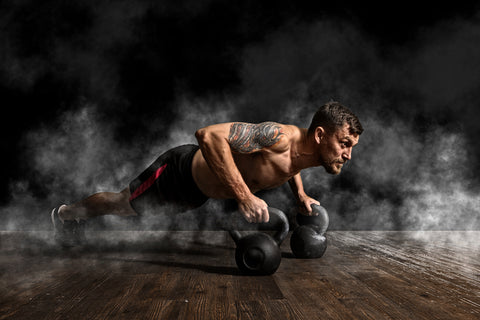 A man doing push ups with dumbbells.