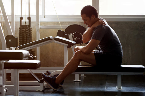 Muscular man suffering from neck injury while exercising at gym