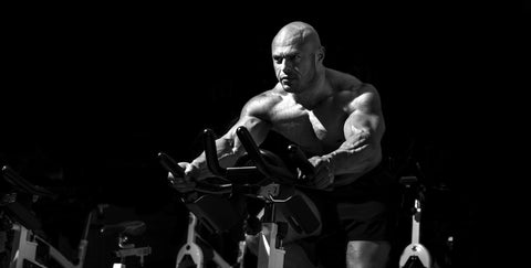 Man bodybuilder perform exercise with exercise bike in dark GYM