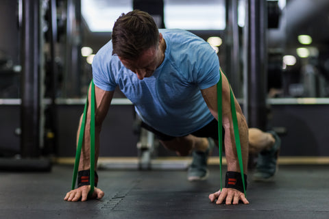Man doing push-up using a elastic band at the gym