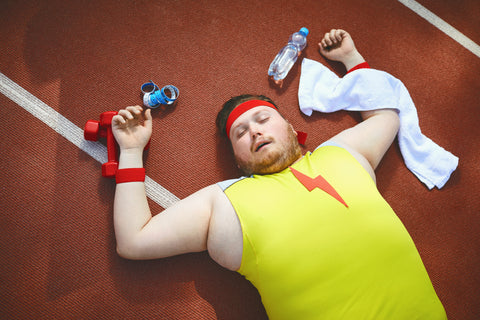 Fat lazy man sleeps tired lies on the track in the stadium.