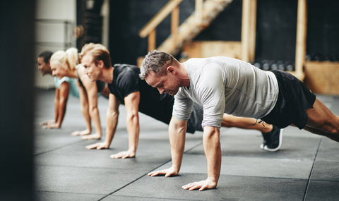A group of people doing push ups in a gym.