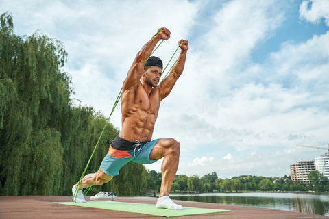 muscular man training outdoors with a resistance band